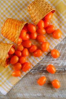Verstreute tomaten aus weidenkörben auf picknicktuch und holztisch. draufsicht.