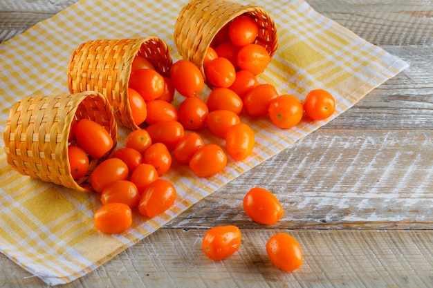Verstreute tomaten aus weidenkörben auf picknicktuch und holztisch. high angle view.