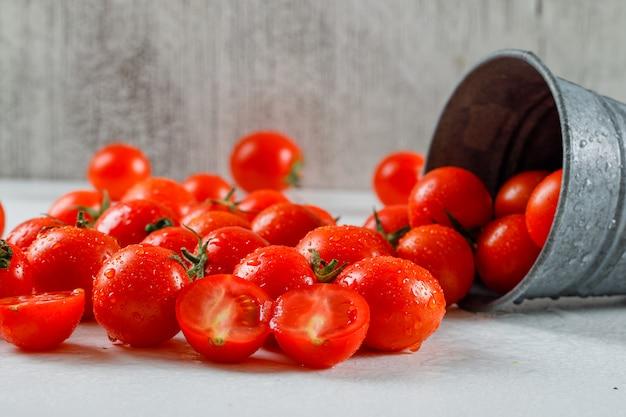 Verstreute tomaten in einem mini-backet auf grauem grunge und weißer oberfläche. seitenansicht.