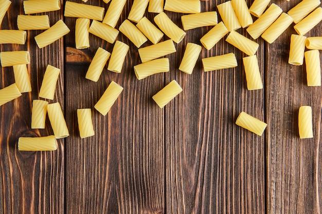 Verstreute tortiglioni-nudeln auf holztisch, flach gelegen.