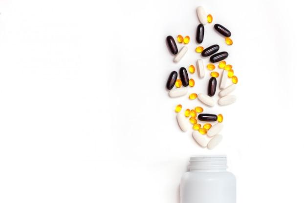 Verstreute vitamintabletten, die aus einer weißen flasche mit kopierraum verschüttet werden. vorteile der einnahme von vitaminen konzept. missbrauchskonzept für nahrungsergänzungsmittel. isolierte bank mit tabletten.