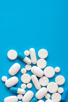 Verstreute weiße pillen auf blauem tisch. medizin-, apotheken- und gesundheitskonzept. speicherplatz kopieren. leerer platz für text oder logo