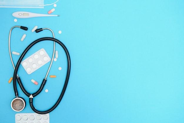 Verstreute weiße pillen auf blauem tisch. medizin-, apotheken- und gesundheitskonzept. weiße pillen des blauen hintergrunds mit einem medizinischen statoskop, draufsicht.