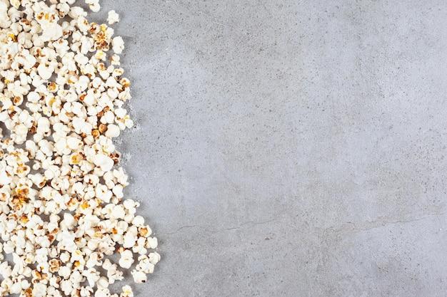 Verstreutes popcorn breitete sich über den marmorhintergrund aus.