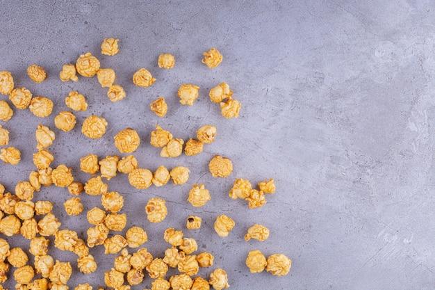 Verstreutes salziges popcorn auf steinoberfläche gelegt