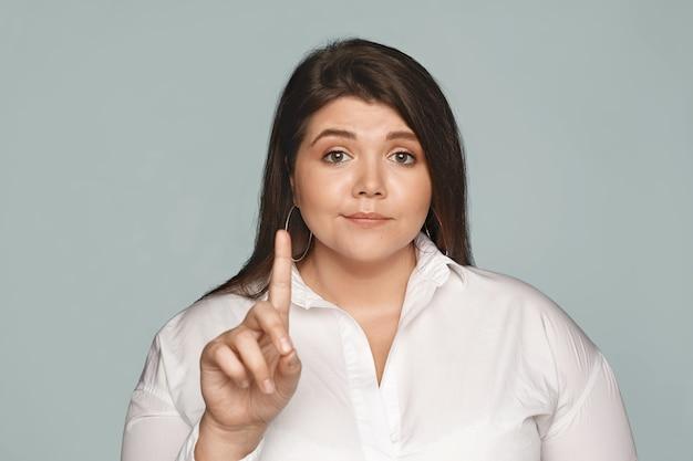 Versuche es nicht einmal. schöne selbstbewusste übergewichtige junge frau mit kurvigem körper und dunklem haar, das zeigefinger schüttelt, keine oder ablehnungsgeste macht, nicht an ihrer meinung interessiert. selektiver fokus