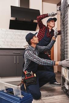 Versuchen sie, diese zwei männer mechaniker zu ficken, die den kühlschrank überprüfen
