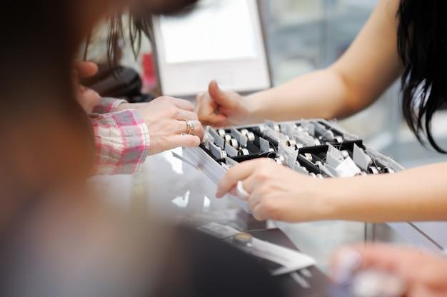 Versuchende eheringe der frau an einem juwelier, fokus an hand