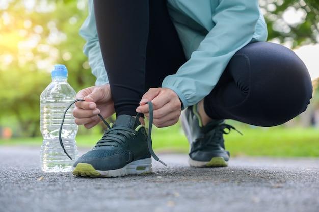 Versuchende laufschuhe des weiblichen läufers mit dem flaschenwasser, das zum lauf fertig wird.
