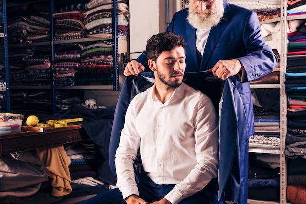 Versuchender mantel des älteren männlichen modedesigners über seinem kunden im shop