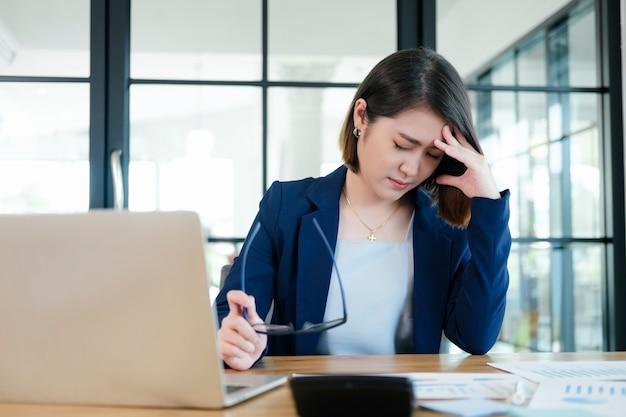 Versuchte junge büroangestellte der geschäftsfrau am schreibtisch beim versuch, im modernen büro zu arbeiten.
