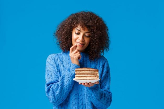 Versuchung, sportclub und kalorien-konzept. mädchen kann nicht widerstehen, aber möchte versuchen, köstlichen nachtisch zu beißen, fingernagel zu beißen und mit dem wunsch stückkuchen zu betrachten, blaue zugwillenskraft stehend