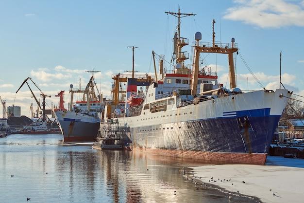 Vertäut frachtschiffe und hafenkräne im hafen. seehafen, frachtcontainerwerft, containerschiffsterminal, werft. wirtschaft und handel, logistik. winter-industrieszene.