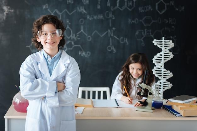 Verteidigung unseres chemieprojekts. lächelnd entzückter qualifizierter junge, der im labor steht und positivität ausdrückt, während sein klassenkamerad am scince-projekt arbeitet