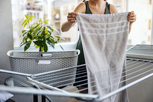 Verteilen sie die wäsche auf der terrasse. eine frau breitet an einem sonnigen tag ein gewaschenes handtuch auf dem gestell zum trocknen auf der terrasse aus. hausarbeit und wohnungs- und haushygiene. die frau macht die hausarbeit