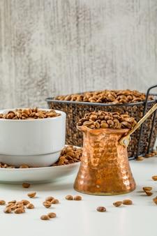 Verteilen sie frische kaffeesamen in kaffeekanne, tasse und schwarzem sieb auf einer weißen und schmutzigen wand. seitenansicht.