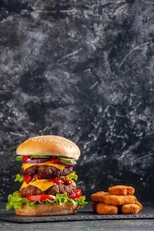 Vertica ansicht des leckeren fleischsandwiches mit tomatengrün auf dunklem farbtablett und hühnernuggets auf schwarzer oberfläche