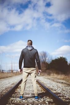 Vertikal eines mannes, der die bibel hält, während er auf einem bahngleis mit einer unschärfe steht
