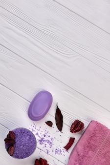Vertikal geschossenes lila badzubehör auf weißem schreibtisch.