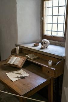 Vertikal von einem dichterzimmer mit einem schädel, papieren und einem buch auf dem schreibtisch