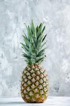Vertikale ansicht der ganzen frischen goldenen ananas, die auf marmoroberfläche steht
