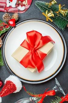 Vertikale ansicht der geschenkbox auf dem teller der weihnachtsbaum-tannenzweige nadelbaumkegel-weihnachtsmannhut gefallener glasbecher auf schwarzem hintergrund