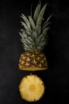 Vertikale ansicht der geschnittenen ananas auf schwarzer oberfläche