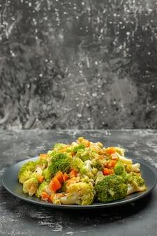 Vertikale ansicht der gesunden mahlzeit mit brocoli und karotten auf einem schwarzen teller mit gabel und messer