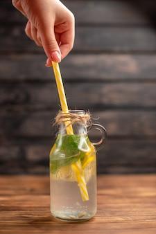 Vertikale ansicht der hand, die ein rohr in einem glas mit frischem detox-wasser auf braunem hintergrund hält