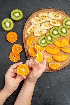 Vertikale ansicht der hand, die eine orangenscheibe aus einem natürlichen organischen frischen obst auf dem schneidebrett und um sie herum auf dunklem hintergrund nimmt