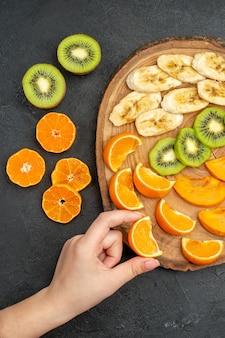 Vertikale ansicht der hand, die eine orangenscheibe aus einem natürlichen organischen frischen obst auf einem schneidebrett auf dunklem hintergrund nimmt