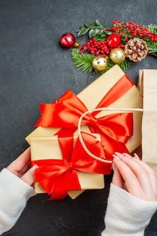 Vertikale ansicht der hand, die eine schöne geschenkbox aus einer tasche auf schwarzem hintergrund herausnimmt