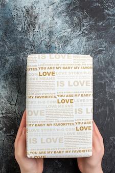 Vertikale ansicht der hand, die eine schöne geschenkbox für einen geliebten menschen auf dunklem hintergrund mit freiem platz hält