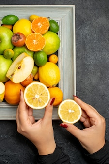 Vertikale ansicht der hand, die geschnittene zitronen aus der sammlung von ganzen und geschnittenen frischen früchten im bilderrahmen auf schwarzem tisch hält