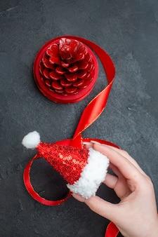 Vertikale ansicht der hand, die weihnachtsmannhut und roten nadelbaumkegel auf dunklem hintergrund hält