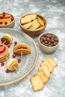 Vertikale ansicht der hausgemachten pfannkuchendekoration und der kekse auf weißem teller und weiß