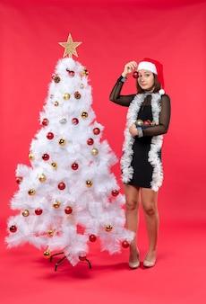 Vertikale ansicht der jungen frau in einem schwarzen kleid mit weihnachtsmannmütze und verziertem weihnachtsbaum auf rot
