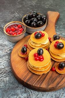 Vertikale ansicht der klassischen amerikanischen pfannkuchen, die mit früchten auf schneidebrett serviert werden