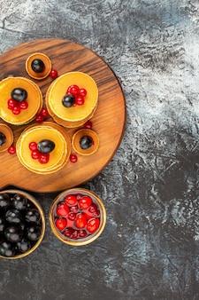 Vertikale ansicht der klassischen buttermilchpfannkuchen, die mit früchten gedient werden