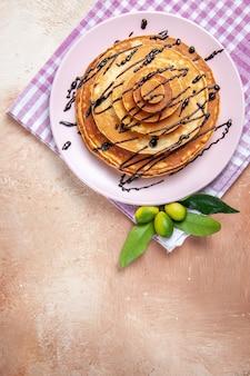 Vertikale ansicht der klassischen köstlichen pfannkuchen, die mit schokoladensyrop auf rosa abgestreiftem handtuch verziert werden