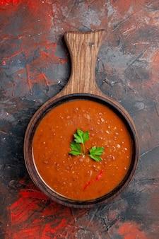 Vertikale ansicht der klassischen tomatensuppe auf einem braunen schneidebrett auf gemischtem farbhintergrund