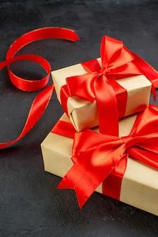 Vertikale ansicht der schönen geschenke mit rotem band auf dunklem hintergrund