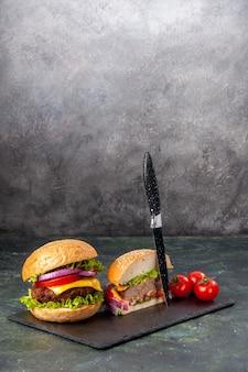 Vertikale ansicht des ganzen schnitts verschiedene leckere sandwiches und tomaten mit stielmesser auf schwarzem tablett auf dunkler mischfarboberfläche