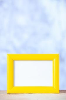 Vertikale ansicht des gelben leeren bilderrahmens, der auf dem tisch auf aquarellhintergrund steht