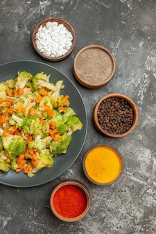 Vertikale ansicht des gemüsemehls mit brokkoli und karotten auf einem schwarzen teller und gewürzen auf grauem tisch