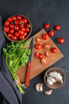 Vertikale ansicht des grünen bündels frischer tomaten auf hölzernem schneidebrett und im schüssel knoblauchhandtuch auf schwarzer notleidender oberfläche