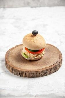 Vertikale ansicht des hausgemachten köstlichen sandwichs mit schwarzer olive auf holzschneidebrett auf befleckter weißer oberfläche