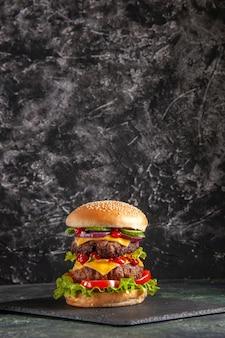 Vertikale ansicht des köstlichen fleischsandwiches mit tomatengrün auf dunklem farbbehälter auf schwarzer oberfläche