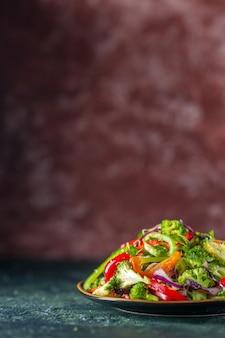 Vertikale ansicht des köstlichen veganen salats mit frischen zutaten in einem teller auf der linken seite auf blauem und kastanienbraunem unscharfem hintergrund