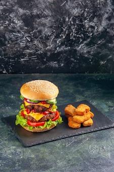 Vertikale ansicht des leckeren fleischsandwiches mit tomatengrün auf dunklem farbtablett und hühnernuggets auf schwarzer oberfläche